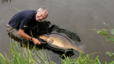 John Bailey, with care and concern, returns Neill Stephen's monster carp Picture: John Bailey