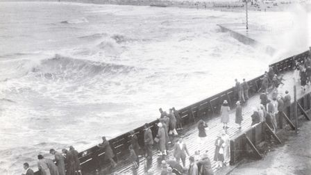A rough sea battering Gorleston Pier attracts sightseers in the era when the White Swan was wrecked.