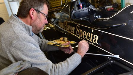 Classic cars being worked on in the workshops at Classic Team Lotus. Signwriter Paul Banham working