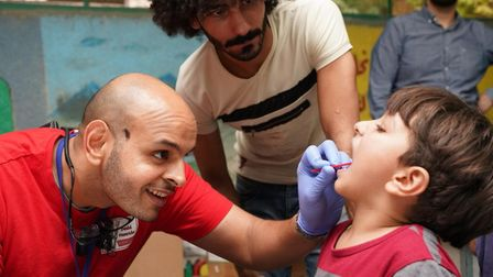 Dr Sharma providing dental care and education during his international mission. Pictures: c/o West E