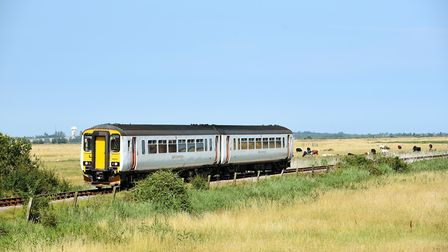 A train on the Reedham to Great Yarmouth line passing through the open marshes near Breydon Water. P