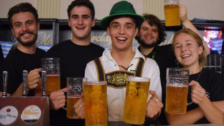Bavarian waiter Leon Harris, with some of the bar staff at the Norwich Oktoberfest at the Open. Pict
