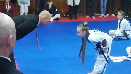 Youngster Aimee Earl collecting her black belt. Picture: Samantha Hawes