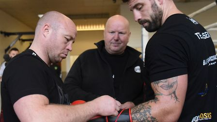 Boxer Sam Sexton gets his gloves on with help from trainers Jon Thaxton, left, and Graham Everett, r