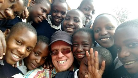 Photographer Julian Claxton with children he taught on his most recent visit to Uganda. Some of thei