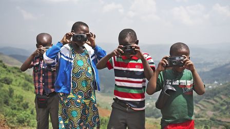 Some of the Ugandan children taught by photographer Julian Claxton practice their new-found skills c