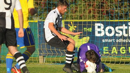 Action from Norwich United against Long Melford. Norwich United goalkeeper Luke Pearson stays on th