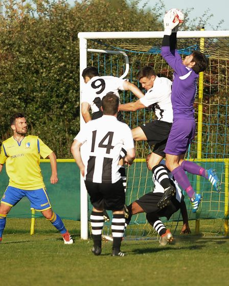 Action from Norwich United against Long Melford. Goalkeeper Luke Pearson and George Watts-Sturrick f