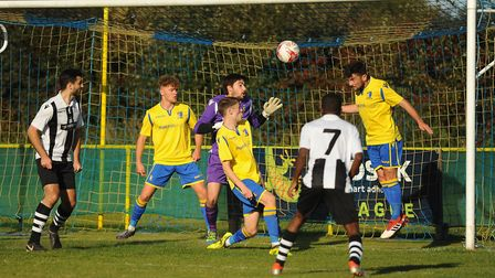 Goalmouth action from Norwich United against Long Melford. From left Norwich United (yellow) players