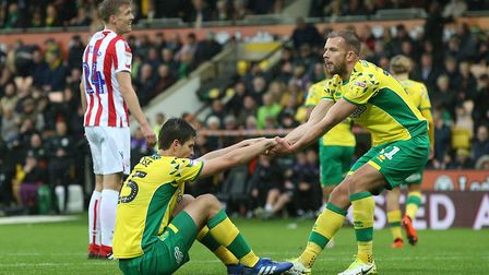 Jordan Rhodes of Norwich helps Timm Klose of Norwich to his feet during the Sky Bet Championship mat