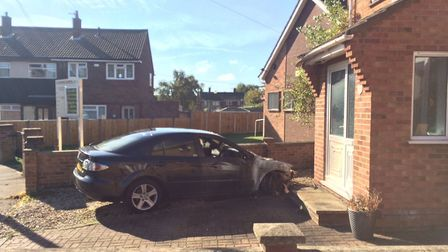 The torched car in the driveway of a house in Antingham Road, Norwich, Picture: David Bale