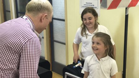 Bethany and Violet check in their luggage with Assistant Headtacher Mr Serruys. Picture: Neil Didsbu