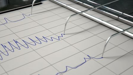 A closeup of lie detector machine needles drawing blue lines on graph paper depicting an interrogati
