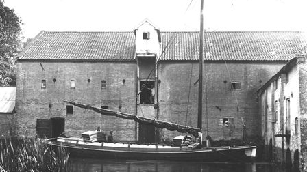 Aylsham watermill in 1910 with a wherry passing in front. Pic: EDP archive.