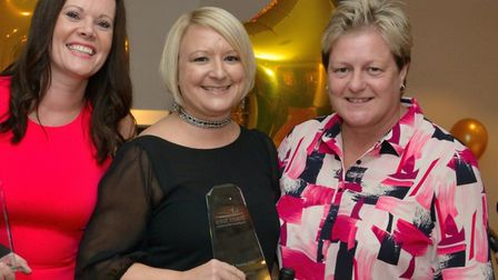 Senior physiotherapist Tanya Fryer (centre) receives an ECCH Champion award from Staff Directors Lis