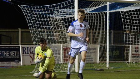 Leiston goalkeeper Charlie Beckwith claims after coming under pressure from Lowestoft's Cion Wren. P