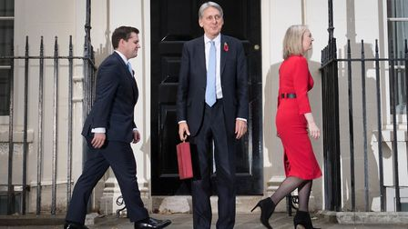 Chancellor Philip Hammond holding his red ministerial box outside 11 Downing Street, London, with Tr