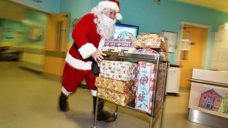 Santa delivering presents, donated to the Send a Smile for Santa appeal, to children on the Buxton W