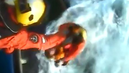 A HM Coastguard rescue helicopter from Humberside winches two fishermen to safety from the deck of t