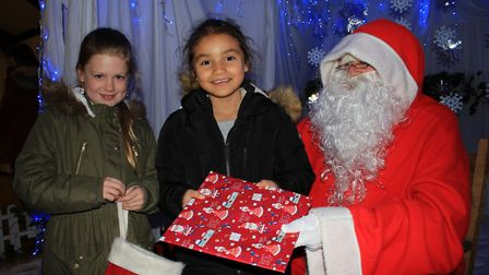 Mia and Jade Andrews visit Father Christmas at his grotto in the parish hall.Photo: KAREN BETHELL