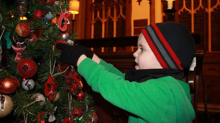 Four-year-old Oliver hanging a decoration on one of the trees on display in Cromer Parish Church.Pho