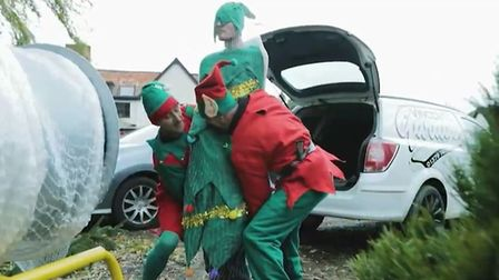 Employees Keith Bickers, Shaun Woodcock and Matt White star as two elves and a Christmas tree in the