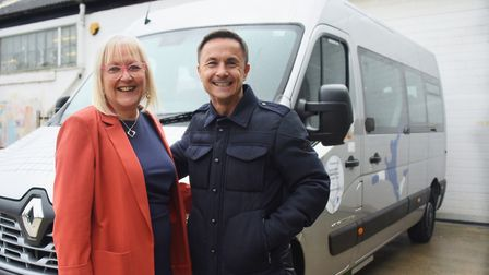 Former Chelsea footballer Dennis Wise, front right, presents a minibus to Lorraine Bliss, front left