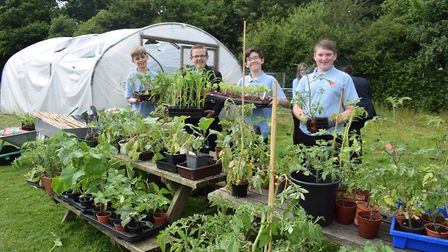 Pupils at Dereham Neatherd High School with plants which were donated after its garden was vandalise
