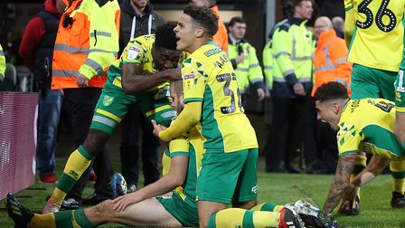 Max Aarons relishes the moment with his Norwich City team-mates, after Teemu Pukki's injury-time goa