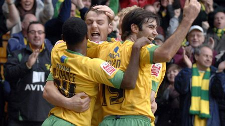 Anthony McNamee, left, and Simon Lappin, right, congratulate Chris Martin on his late Carrow Road wi