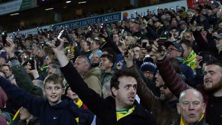 Fans use their phones to light up the ground as floodlight failure halts the match Photo: Paul Che
