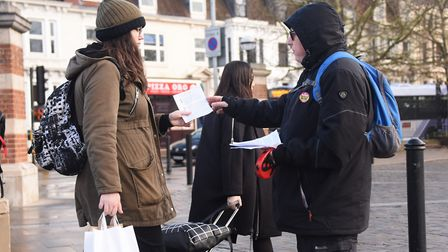 One of the protesters against the rail fares increase, Darrell Hall, right, hands out leaflets to co