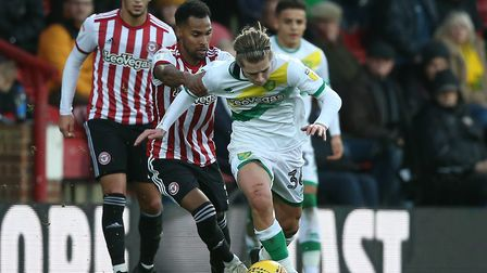 Todd Cantwell tries to wriggle free of Rico Henry as Norwich City claim a Championship point at Bren