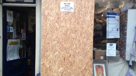 """A sign at the front of the store reads """"We are open. Unfortunately some idiot decided to smash our w"""