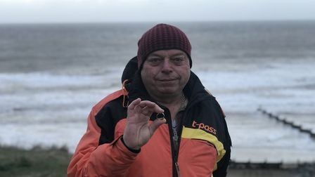 Steve Sandeel holding the engraved ring of Ingrid Fleetcroft that he found on Overstand beach after