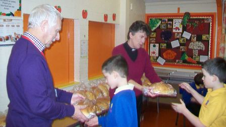 Pupils from Fleggburgh CE Primary School receiving their 'Plough Monday' loaf of bread. The traditio