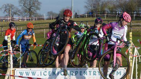 Norwich rider Alison Hogg (red helmet) at the hurdles at the Iceni Velo cyclo-cross at Snetterton Pi