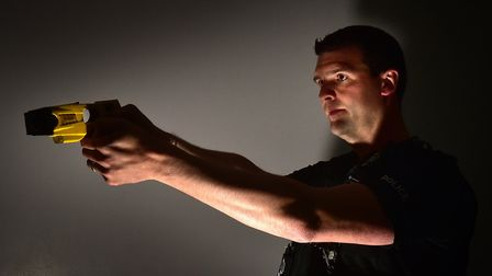 Sgt Chris Harris with a X26 taser gun. Picture: ANTONY KELLY