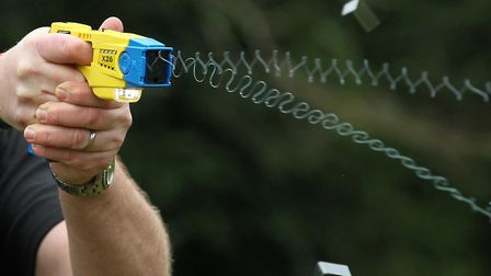 A police officer demonstrating use of Taser. Photo: Gareth Fuller/PA Wire