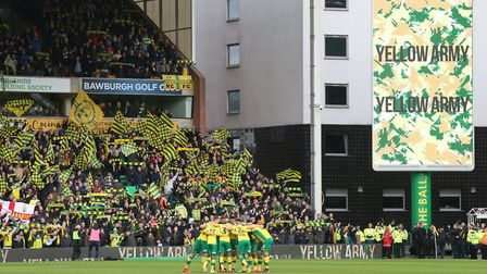 The Norwich players in the pre match huddle in front of the home fans displaying the Yellow and Gree