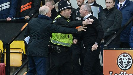 Paul Lambert is restrained by a police officer as tempers flare just before half-time at Carrow Roa