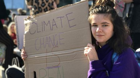 Young protester holds up signs during the Youth Strike 4 Climate demonstration outside The Forum in