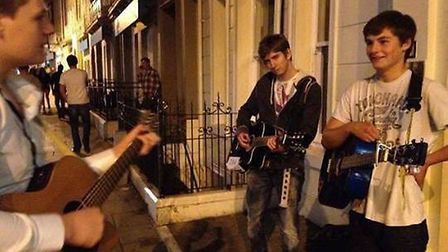Harvey Lewis playing guitar on a Norwich street. His friend, Eric Hewson, has set up a charity in hi