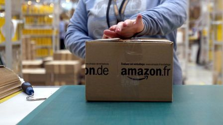 A worker tapes shut a parcel in the Amazon fulfilment centre in Peterborough Cambridgeshire as it p
