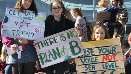 Young protesters hold up signs during the Youth Strike 4 Climate demonstration outside The Forum in
