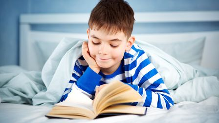 Boy lying in bed with a book. Photo: Getty Images/iStockphoto