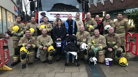 Harry and his parents (centre) with the fire crew from North Earlham fire station, who are doing a n