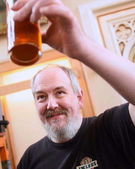 Andy Mitchell, head of technical, checks a sample of one of the Norfolk beers during preparations fo