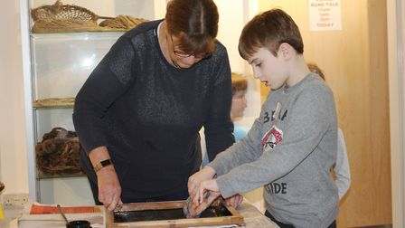 Artist Jill Brammer helps a youngster make a screen printed tee shirt at one of the family workshops