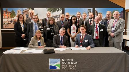 The construction contract being signed by Steve Blatch (sitting, centre), North Norfolk District Cou